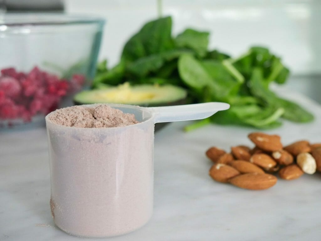 Protein powder with almonds spinach raspberries and avocado behind