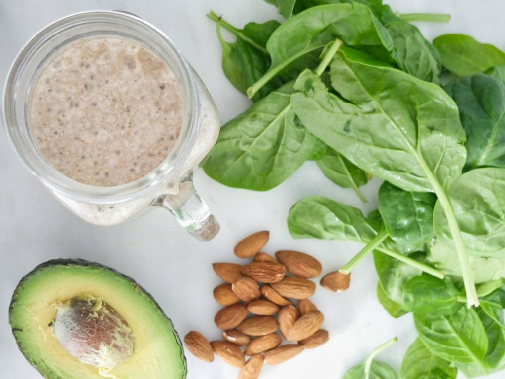 Avocado spinach smoothie displayed with ingredients