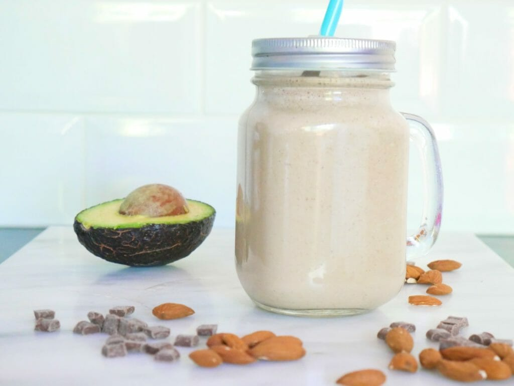 A chocolate almond smoothie with avocado and ingredients around