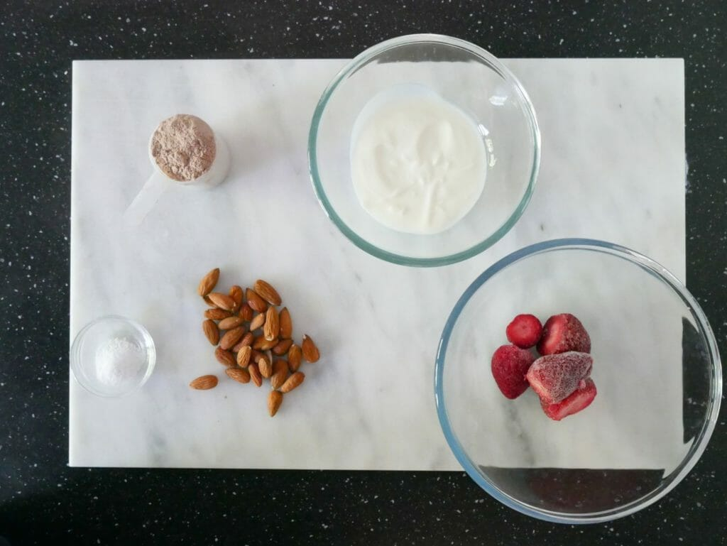 Strawberry chocolate protein shake ingredients on a marble slab