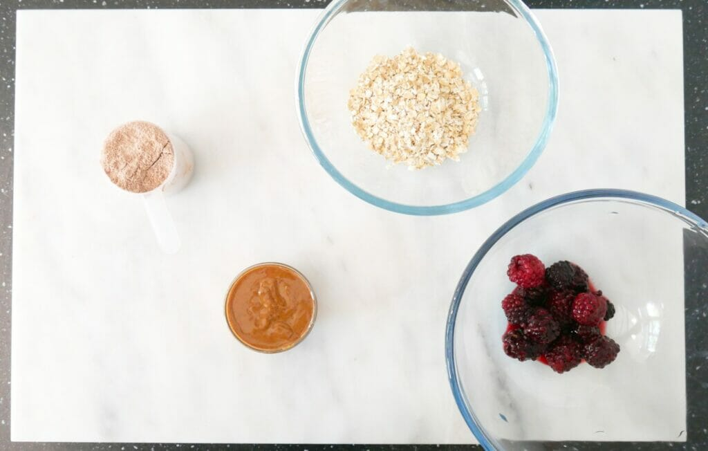 Almond butter and berry protein shake weight gain smoothie ingredients on marble