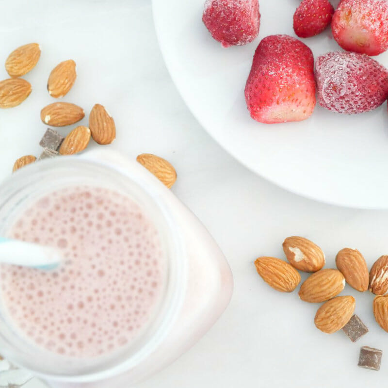 Strawberry protein shake weight loss smoothie with strawberries, almonds, and chocolate chips seen from above
