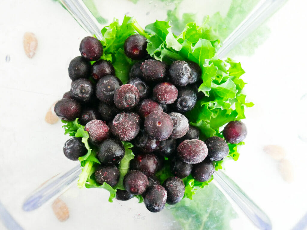 Blueberries and kale in a blender with almond milk