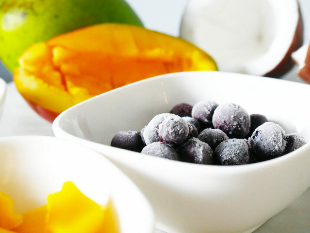 Blueberries in a dish with mango and coconut behind