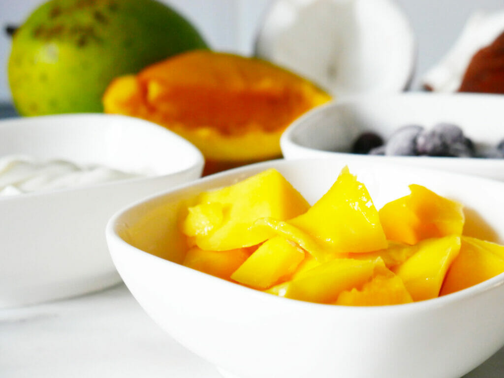 Mango in a dish with other blueberry coconut smoothie ingredients behind