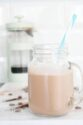Coffee protein shake smoothie with blue straw and green cafetiere behind